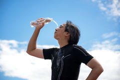 Sport man athletes pour water on their faces and holding a water bottle drinking water after exercise,back ground blue sky. Stock Image