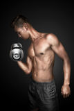 Sport man. Man doing exercising lifting weights on black background Stock Image
