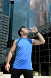 Sport man drinking water bottle after running training session in business district Stock Images