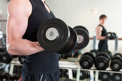 Sport - man is exercising with barbell in gym Stock Photography