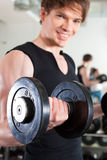 Sport - man is exercising with barbell in gym Stock Images