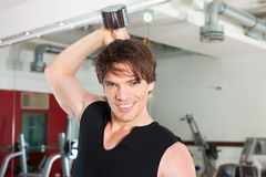Sport - man is exercising with barbell in gym Stock Image