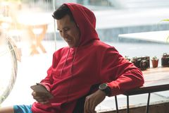 Sport man in red hood listening to music. By smart phone, modern lifestyle concept Stock Photos