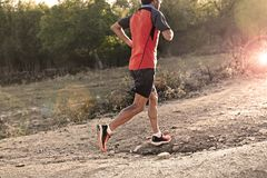 Sport man with ripped athletic and muscular legs running uphill off road in jogging training workout Stock Images