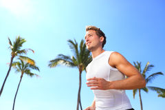 Sport man running. Male athlete runner jogging in compression t-shirt top training on palm trees beach. Fit handsome male fitness model jogging alone training Royalty Free Stock Photography
