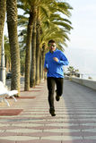 Sport man running along beach palm trees boulevard in morning jog training session Royalty Free Stock Images