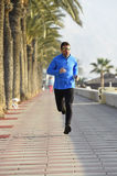 Sport man running along beach palm trees boulevard in morning jog training session Royalty Free Stock Photography