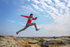 Sport man running, jumping over rocks in mountain area. Stock Photos
