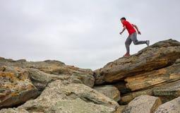 Sport man running, jumping over rocks in mountain area. Stock Photos