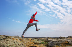 Sport man running, jumping over rocks in mountain area. Stock Photography