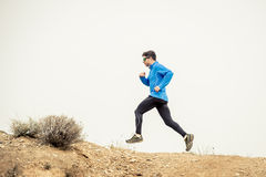 Sport man running on off road trail dirty road with dry desert landscape background training hard Royalty Free Stock Photo