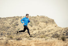 Sport man running on off road trail dirty road with dry desert landscape background training hard. Young sport man running on off road trail dirty road with dry Stock Image
