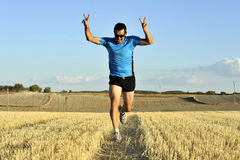 Sport man running outdoors on straw field doing victory sign in frontal perspective. Young sport man with sunglasses running outdoors on straw field ground in stock images