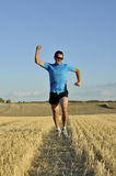 Sport man running outdoors on straw field doing victory sign in frontal perspective Royalty Free Stock Photography