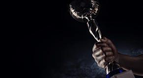 sport Man& x27; s ręka trzyma up złocistą trofeum filiżankę obraz royalty free