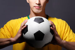 Sport man smile and holding soccer. Young sport man smile and holding soccer isolated on gray background Stock Photography