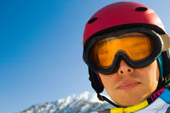 Sport man in snowy mountains. An image with a portrait of a snowboarder wearing a helmet and glasses on the background of high snow-capped Alps in Grindelwald Stock Photography