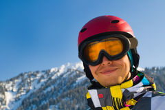 Sport man in snowy mountains. An image with a portrait of a snowboarder wearing a helmet and glasses on the background of high snow-capped Alps in Grindelwald Stock Photos