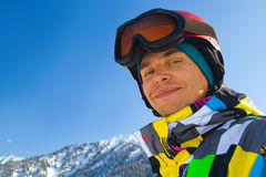 Sport man in snowy mountains. An image with a portrait of a snowboarder wearing a helmet and glasses on the background of high snow-capped Alps in Grindelwald Royalty Free Stock Photography