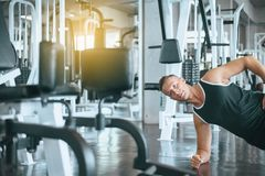 Sport man stretching for warming up befor doing plank exercises training,Cross fit body muscular workout in the gym royalty free stock photography
