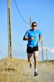 Sport man with sun glasses running on countryside track with power line poles Stock Photography