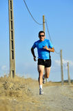 Sport man with sun glasses running on countryside track with power line poles Royalty Free Stock Photo