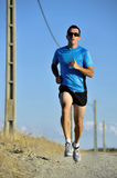 Sport man with sun glasses running on countryside track with power line poles Stock Image