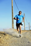 Sport man with sun glasses running on countryside track with power line poles Stock Images