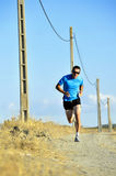 Sport man with sun glasses running on countryside track with power line poles Stock Photos
