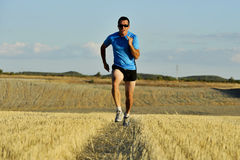 Sport man with sunglasses running outdoors on straw field ground in frontal perspective Stock Photography