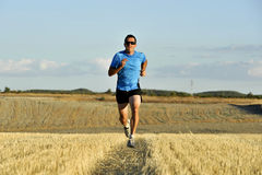Sport man with sunglasses running outdoors on straw field ground in frontal perspective Royalty Free Stock Photography