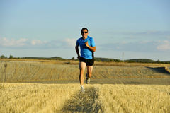 Sport man with sunglasses running outdoors on straw field ground in frontal perspective. Young sport man with sunglasses running outdoors on straw field ground royalty free stock image