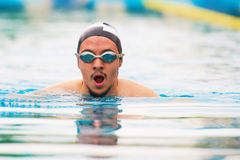 Sport man swim in pool. Portrait of young man in swimming goggles stock images