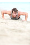 Sport man training push ups. On beach. Young hand some caucasian fitness model in his twenties working out outside on beach Royalty Free Stock Image