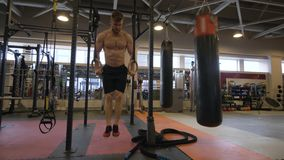 Sport man training workout exercise on gymnastic rings in fitness club. Athlete man doing gym exercise on fitness rings on crossfit training stock video