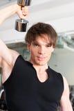 Sport - mannen övar med skivstången i idrottshall Royaltyfri Bild