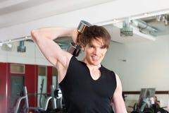 Sport - mannen övar med skivstången i idrottshall Royaltyfria Foton