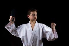 Sport martial de karaté avec le jeune garçon dans le kimono, fond noir, combat photographie stock