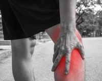 Sport men injury. male athlete jogger wearing man runner massaging calf muscle before workout.  stock photography