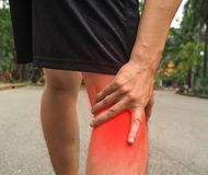 Sport men injury. male athlete jogger wearing man runner massaging calf muscle before workout.  stock photo