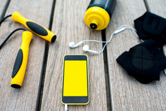 Sport mobile application. Mobile phone with empty screen on the wooden desk surrounded with sport equipment. Sport mobile application concept Stock Image