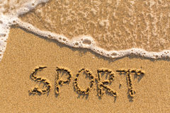 Sport - mot dessiné sur la plage de sable Photographie stock libre de droits