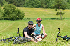 Sport mountain biking couple relax sunny meadows. Sport mountain biking couple relax in meadows sitting drink water royalty free stock photo