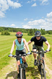 Sport mountain biking - man pushing young girl Royalty Free Stock Photography