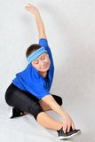 Sport nonstop. Woman performs an exercise fitness holding up the leg and drawing out the the muscles Royalty Free Stock Images