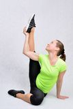 Sport nonstop. Woman performs an exercise fitness holding up the leg and drawing out the the muscles Royalty Free Stock Image