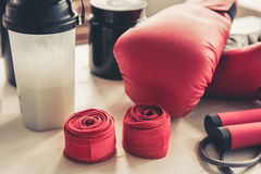 Sport nutrition and equipment. Bottles of sport nutrition and boxing gloves and other sport equipment Royalty Free Stock Photos