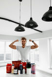 Sport Nutrition. Healthy Man With Bodybuilding Supplements. Nutrition Supplements. Healthy Fitness Man In Kitchen With Sports Powder Drinks Bottles, Containers stock image