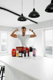 Sport Nutrition. Healthy Man With Bodybuilding Supplements. Nutrition Supplements. Healthy Fitness Man In Kitchen With Sports Powder Drinks Bottles, Containers stock photography