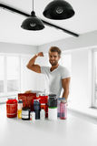 Sport Nutrition. Healthy Man With Bodybuilding Supplements. Nutrition Supplements. Healthy Fitness Man In Kitchen With Sports Powder Drinks Bottles, Containers royalty free stock photos
